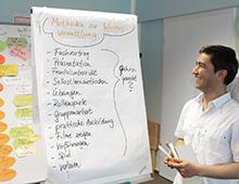 Train the Trainer-Fortbildung: lachender Teilnehmer am Flipchart
