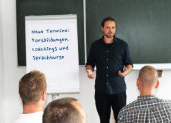 Bild mit Dozent und Tafel mit Text Neue Termine: Fortbildungen, Coachings und Sprachkurse